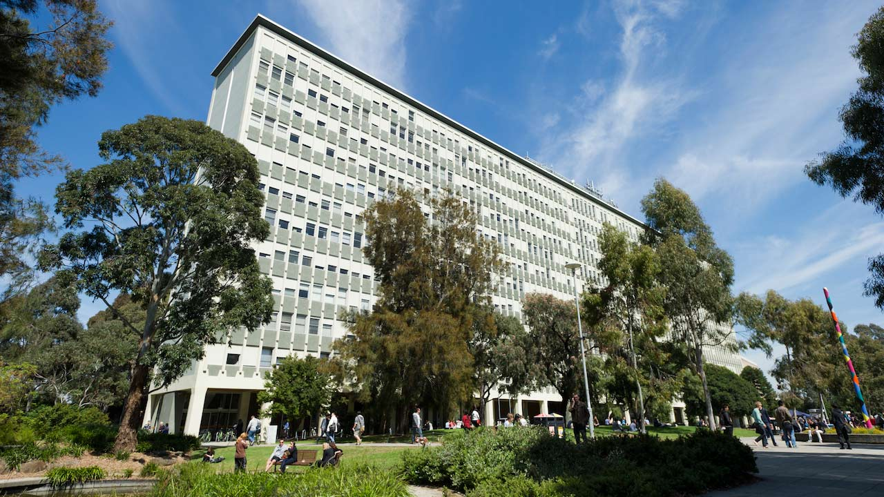 People walk on the pathway and sit on a bench on Monash's campus beneath a large gray building
