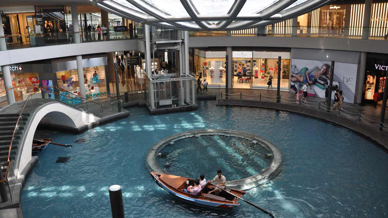 A man rows a canoe on a small body of water inside a mall in Singapore