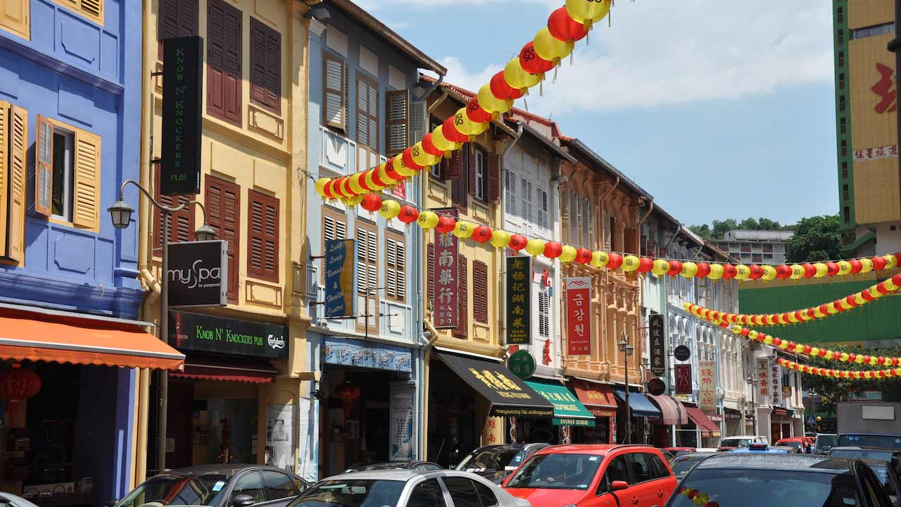 Yellow and red flags hang between buildings on a tiny street in Singapore