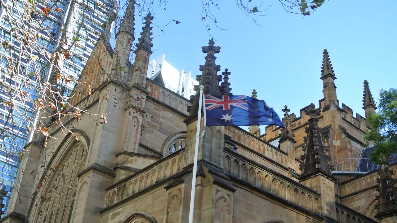The Australian flag waves in the wind in front of an ornate church in Sydney