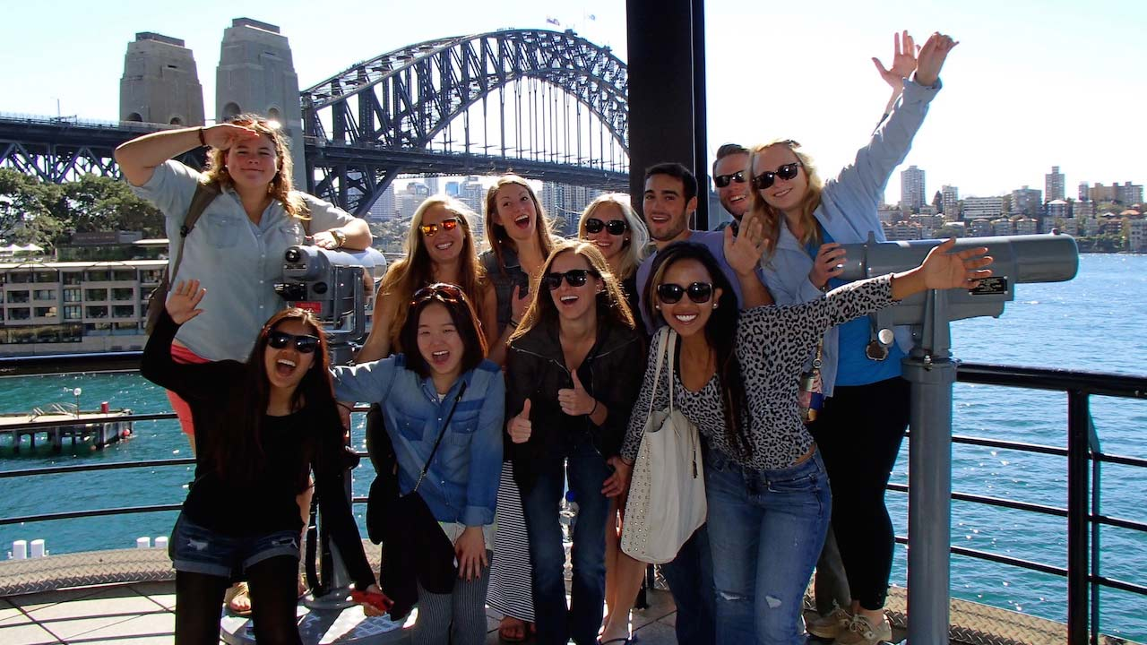 A group of students pose enthusiastically in front of the Sydney Bridge