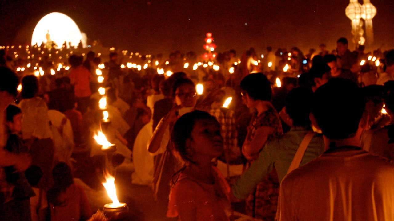 Crowds of people hold candles for a nighttime ceremony in Thailand