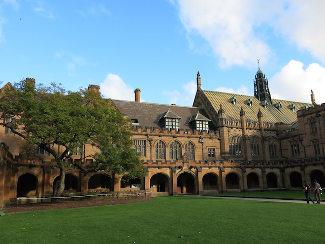 A group of students walk toward a large, ornate building on University of Sydney's campus