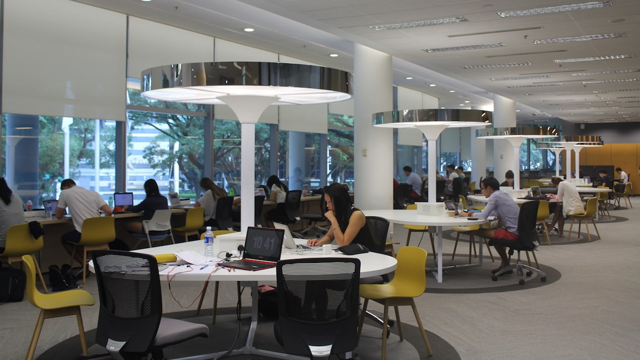 Students sit around round tables in a study room at Singapore Management University