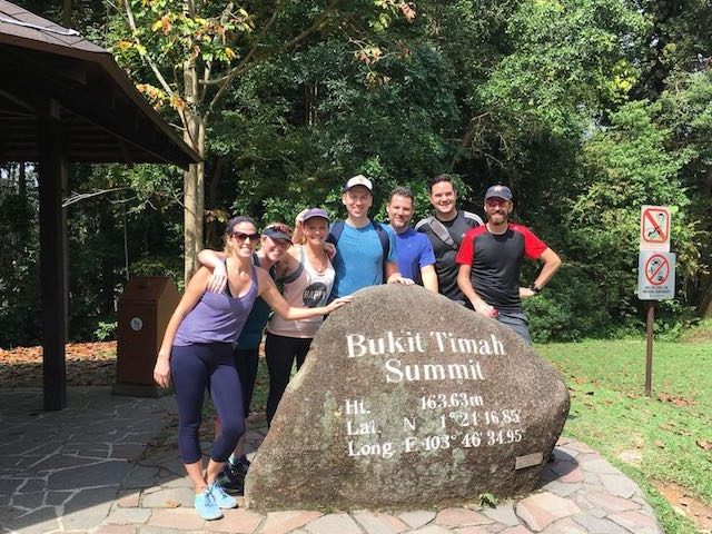Group of people standing in front of Bukit Timah Summit sign